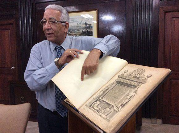 El doctor Eduardo Torres Cuevas hojea las páginas del atlas Theatrum Orbis Terrarum, una de las piezas más valiosas del patrimonio nacional. Foto: María del Carmen Ramón/ Cubadebate.