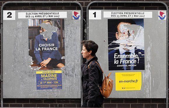 Algunos creen que estos políticos representan el cambio en Francia, otros consideran que la política gala seguirá desgastada no importa quién gane las elecciones. Una mujer camina cerca de carteles desgastados con el mensaje de Marine Le Pen (izq.) y Emmanuel Macron. Foto:  Getty Images.