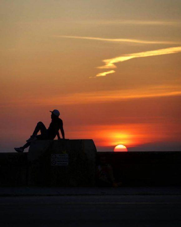 Sentado en el Malecón durante un mágico atardecer en La Habana. Foto: Desmond Boylan (Tomada de su pagina de Facebook)