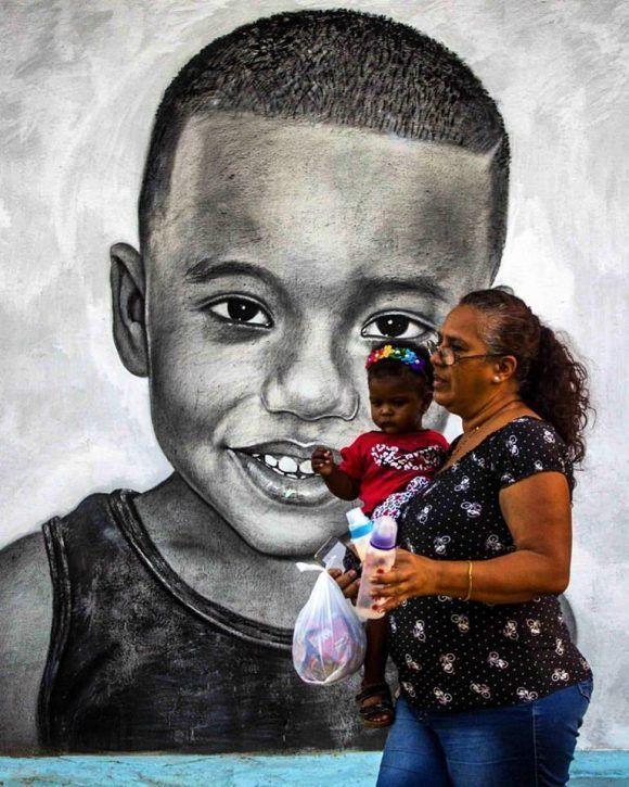Mujer y niño pasan delante de un mural pintado por el artista Maisel Lopez en un muro de La Habana. Foto: Desmond Boylan (Tomada de su pagina de Facebook)